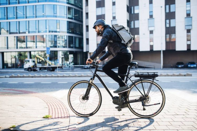 Male hipster courier with bicycle cycling on a road in city, delivering packages. Copy space.